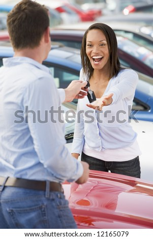Woman collecting keys to new car from salesman - stock photo