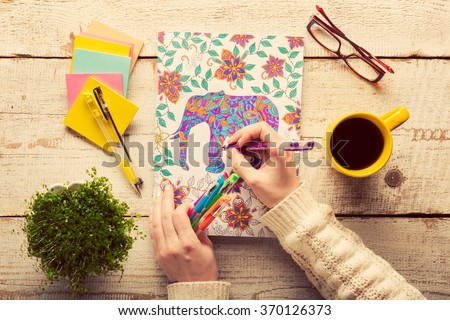 Woman coloring an adult coloring book, new stress relieving trend, mindfulness concept, hand detail - stock photo