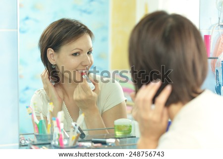 Woman comb her hair in a bathroom - stock photo