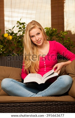 Woman comfortable sitting on sofa surrounded with lemon tree and other green plants and reading book. - stock photo