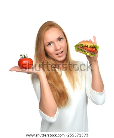 Woman comparing tasty unhealthy burger sandwich in hand and tomato getting ready to eat isolated on a white background Fast food concept - stock photo