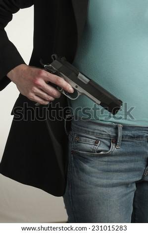 Woman Conceals Gun - stock photo