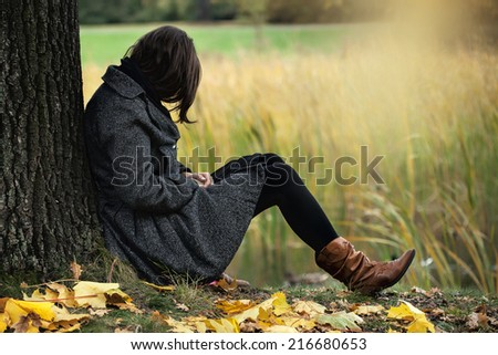 Woman contemplating alone in the autumn park - stock photo