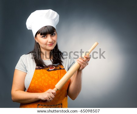 woman cook holding a rolling pin - stock photo
