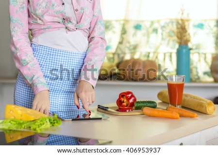 Woman cooking Dish with Cheese Salad Carrot Cucumber ad red Pepper following Recipe on screen of Tablet PC in domestic Kitchen Interior and warm Sunlight throw Window - stock photo