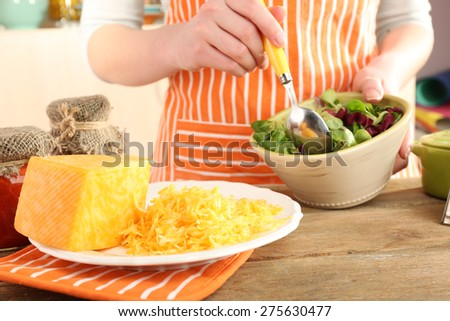 Woman cooking salad with grating cheese, close-up - stock photo