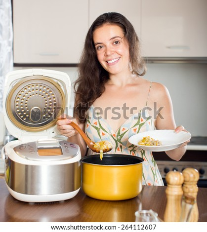 Woman cooking soup with slo-cooker and smiling at kitchen - stock photo