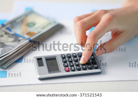 Woman counting money and working on  calculator at the table - stock photo