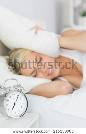Woman covering ears with pillow in bed and alarm clock on side table - stock photo