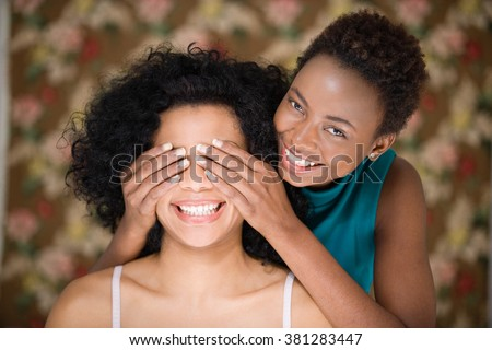 Woman covering friends eyes - stock photo