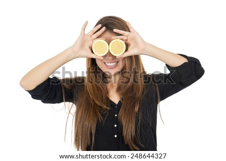 Woman covering her eyes up with lemon slices against a white background - stock photo