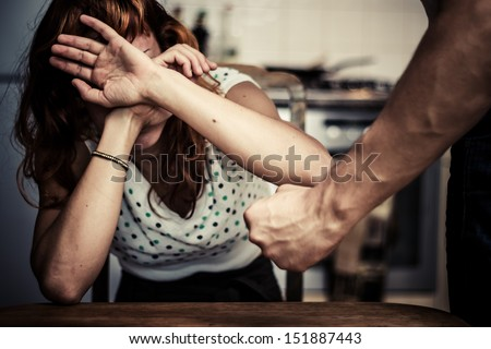 Woman covering her face in fear of domestic violence - stock photo
