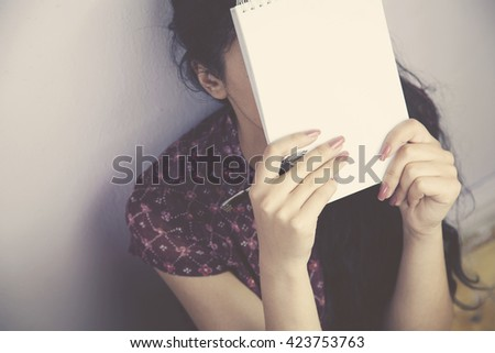 woman covering her face with a notebook - stock photo