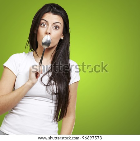 woman covering her mouth with a spoon against a green background - stock photo