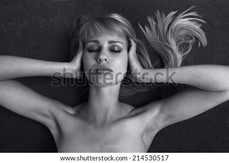 Woman covers ears to block out sound, noise pollution concept - stock photo