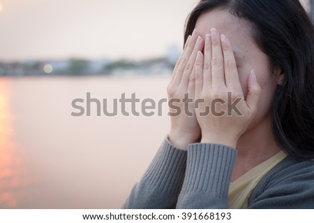 Woman covers her face with hands. selective focus (sunset light) - stock photo
