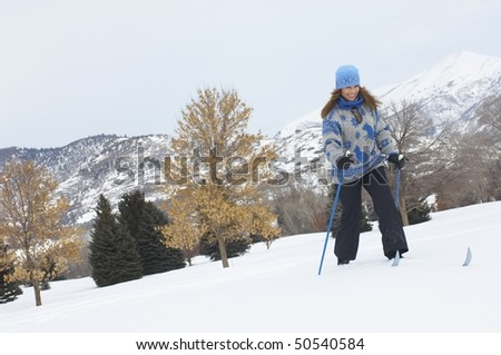 Woman cross-country skiing in snow covered field - stock photo