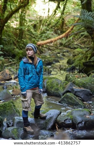Woman crossing a stream in the woods - stock photo