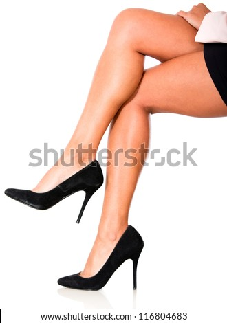 Woman crossing legs and wearing high-heels isolated over white - stock photo