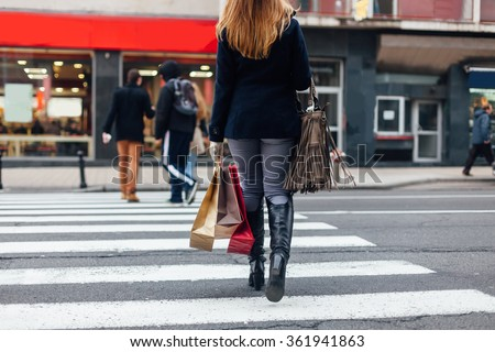 Woman crossing the street at the pedestrian crossing after shopping - stock photo