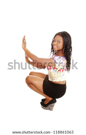 Woman crouching on floor holding on a wall with both hands, in a black skirt and colorful blouse, for white background. - stock photo