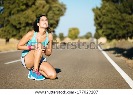 Woman crying for a painful knee injury during running training. - stock photo