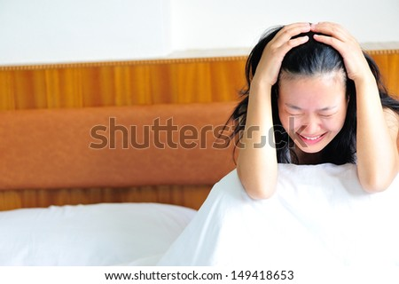 woman crying sitting on the bed clawing her head in sad - stock photo
