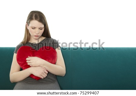 Woman cuddling with a heart pillow - stock photo