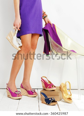 woman cut face photo with a great body and dress holding a shoe in her hands and with other shoes around her - stock photo