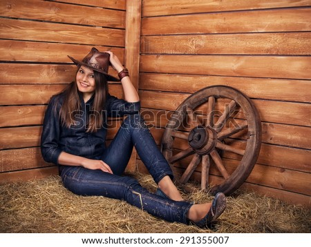 Woman cute seductive cowboy cowgirl on wooden background  in garden as symbol concept of beauty, rodeo, skill, seduction, sex, youth, adolescence, america, agriculture, ecology, farming, usa culture - stock photo