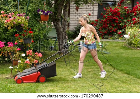 Woman cuts the grass with an electric lawn mower - stock photo