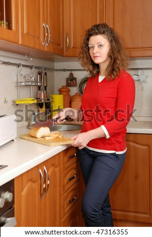 woman cutting bread at kitchen - stock photo