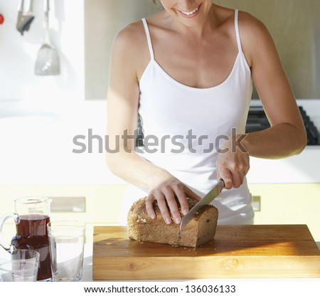 Woman cutting bread on the kitchen - stock photo