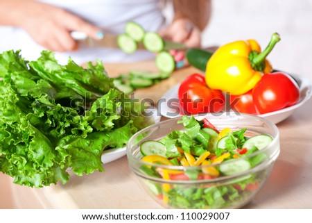 woman cutting  fresh green cucumber for salad, horizontal - stock photo