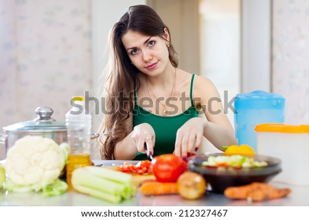woman cutting tomato anf other vegetables in  kitchen   - stock photo