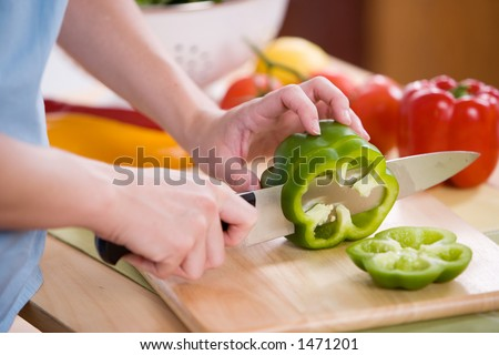 Woman cutting vegetables for a salad. - stock photo