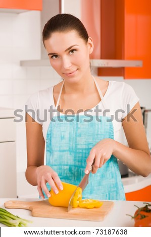 Woman cutting vegetables in a kitchen - stock photo