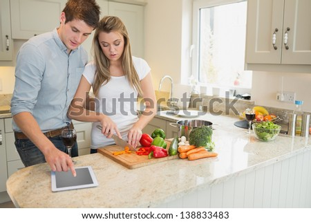 Woman cutting vegetables with man using tablet computer in kitchen - stock photo