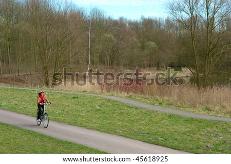 Woman cycling in a park. - stock photo