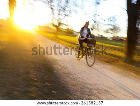 Woman cycling in park at sunset. Blurred motion. - stock photo