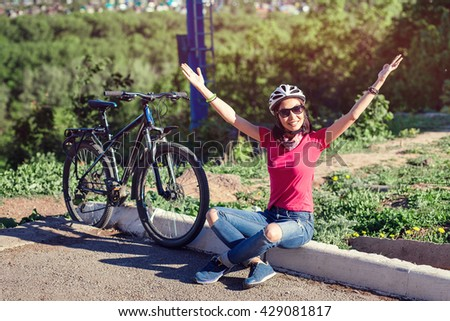 Woman cycling reaching goal raising arms at sunset cheering. - stock photo