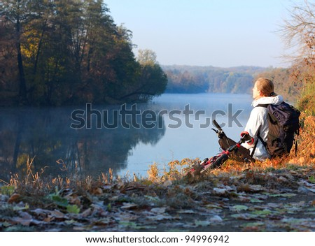 Woman cyclist enjoy the recreation on the lake side illuminated by the rays of the rising sun - stock photo