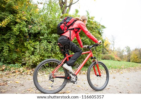 Woman cyclist riding a bike on road in autumn park against the background of green nature - stock photo