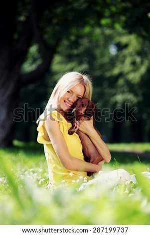 woman dachshund in her arms on grass - stock photo