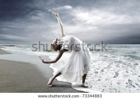 Woman dancer posing on the beach - stock photo
