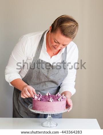 woman decorating a cake - stock photo