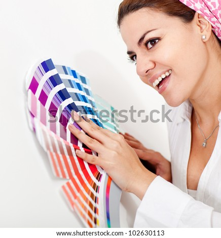 Woman decorating her house and with a color guide to paint the wall - stock photo