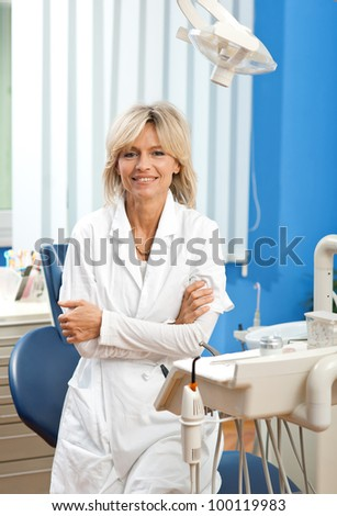 woman dentist in her office smiling - stock photo