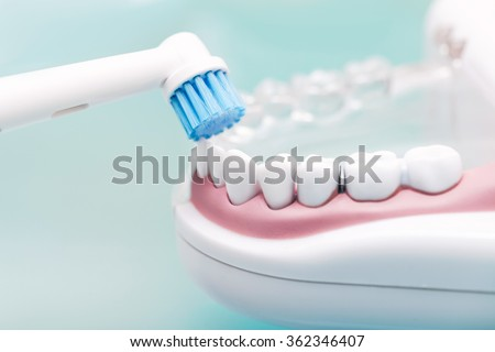 Woman dentist with gloves showing on a jaw model how to clean the teeth with tooth brush properly and right - stock photo