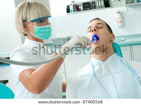 woman dentist with mask working on male patient teeth - stock photo